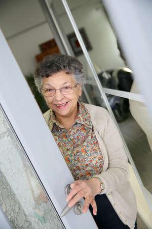 Bejaarde vrouw opening thuis toegangsdeur Stockfoto
