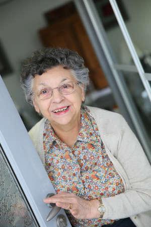 Elderly woman opening home entrance door