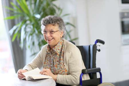 Bejaarde in rolstoel leesboek Stockfoto