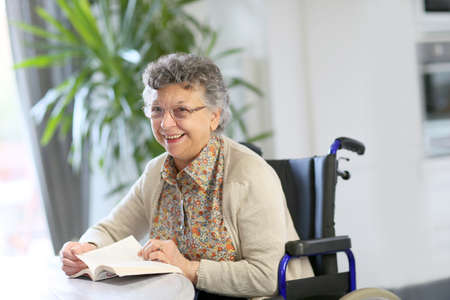 handicap people: Elderly woman in wheelchair reading book