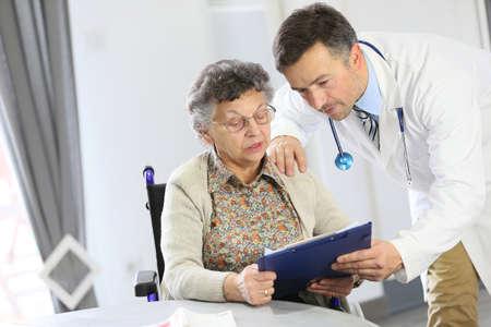 Arts met een bejaarde vrouw in verpleeghuis