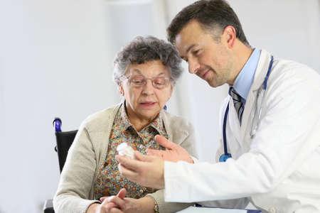 medecine: Doctor with elderly woman showing medical prescription
