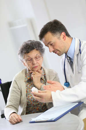 medicalcare: Doctor with elderly woman showing medical prescription