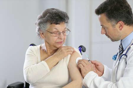ESQUEMA DE VACUNACION: Doctor haciendo inyección de la vacuna a anciana Foto de archivo
