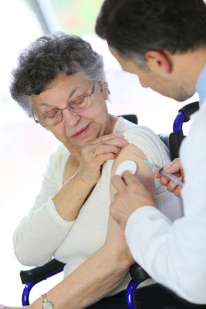 Doctor doing vaccine injection to elderly woman