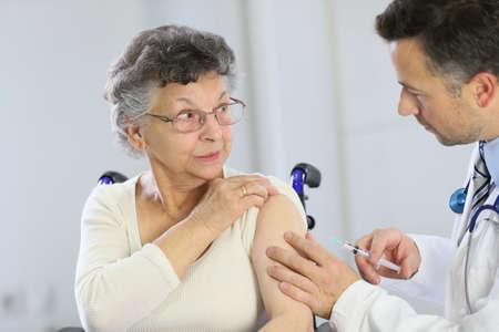 Doctor haciendo inyección de la vacuna a anciana Foto de archivo