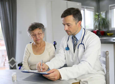 medicalcare: Doctor writing medical prescription for elderly woman Stock Photo