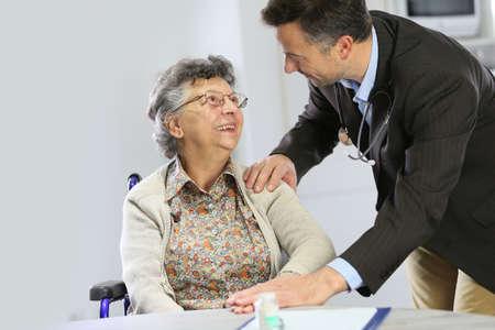 medicalcare: Doctor reassuring elderly woman in wheelchair