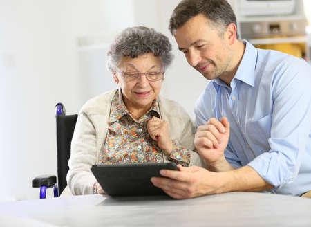 persona en silla de ruedas: Hombre con mujer mayor que usa la tableta digital,