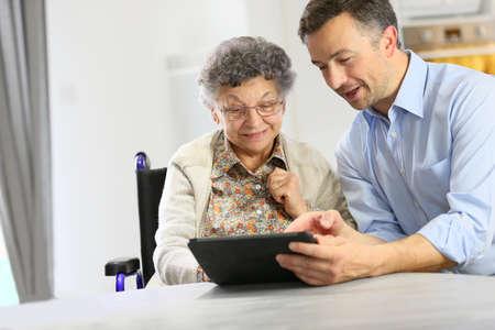 apoyo familiar: Hombre con mujer mayor que usa la tableta digital,