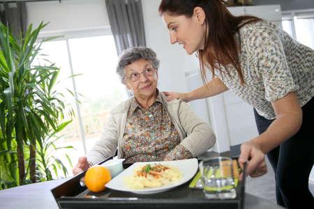 Homecarer preparing lunch for elderly woman photo