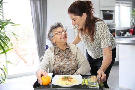 apoyo familiar: Homecarer prepara el almuerzo para la mujer mayor