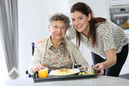 trays: Homecarer preparing lunch for elderly woman