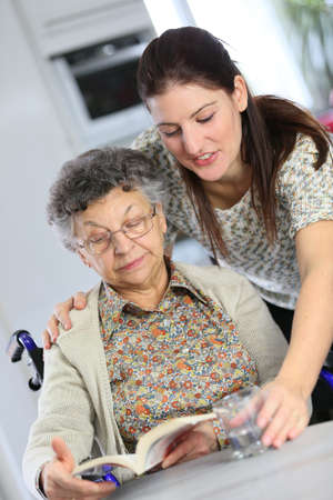 Portrait of elderly woman in wheelchair with home carer photo