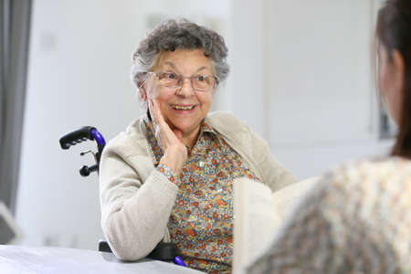 Homec arer reading book to old woman in nursing home photo