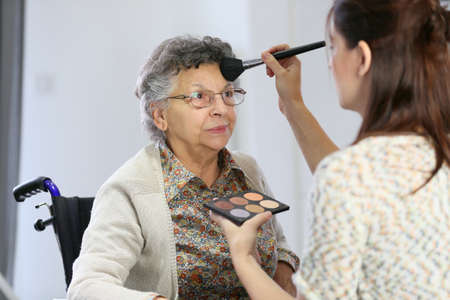 disabled seniors: Home carer helping elderly woman to put makeup on Stock Photo
