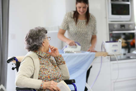 Elderly woman reading book while home helper irons laundry