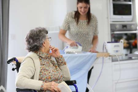 Anciana leyendo libro mientras ayudante a domicilio hierros de lavandería Foto de archivo