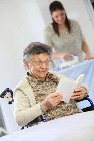 Bejaarde vrouw lezen boek terwijl thuis helper strijkt wasgoed
