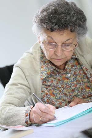 autonomia: Anciana en silla de ruedas llenando el formulario médico