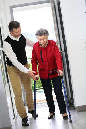 fisico: Hombre que ayuda a anciana con muletas