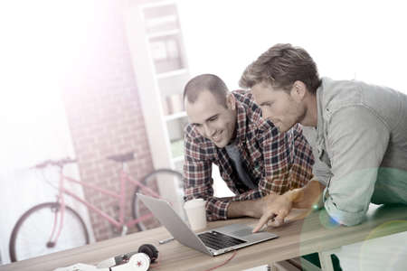 roommates: Young men studying in front of laptop