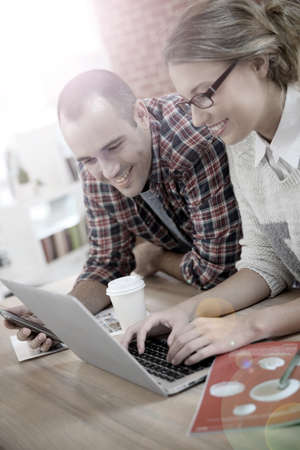 roommates: Young people at home websurfing on laptop