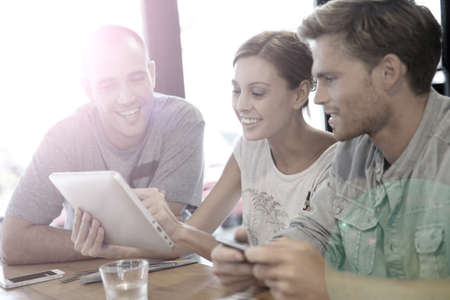roommates: Students in campus lounge websurfing on tablet Stock Photo