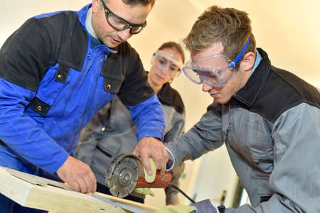 Students learning how to use ceramic saw