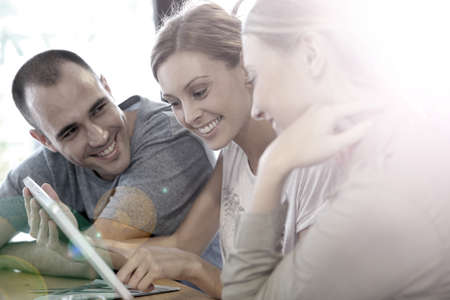 roommates: Group of friends in campus lounge websurfing with tablet