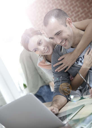 shared sharing: Cheerful couple websurfing on internet with laptop Stock Photo