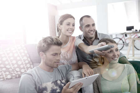 shared sharing: Roommates in apartment watching tv Stock Photo