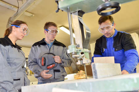 woodwork: Group of students learning how to use woodwork machine Stock Photo