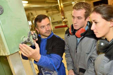 machinery: Professional teacher showing carpentry machinery to students