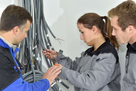 Professional electrician with students on construction site