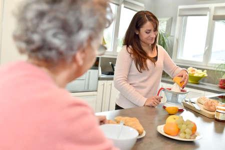 helpers: Home helper serving breakfast to elderly woman Stock Photo