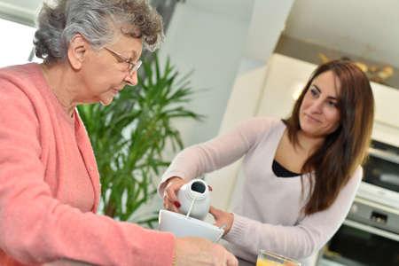 Home helper serving breakfast to elderly woman photo