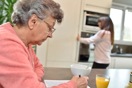 homecare: Elderly woman doing crosswords while homecare helps at home