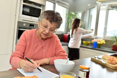 crosswords: Elderly woman doing crosswords while homecare helps at home