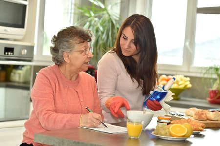 Homecare helping elderly woman doing crossword photo