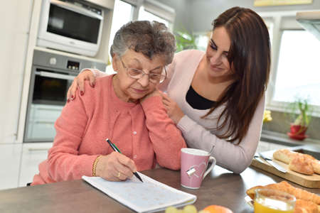 helps: Elderly woman doing crossword while homecare helps at home