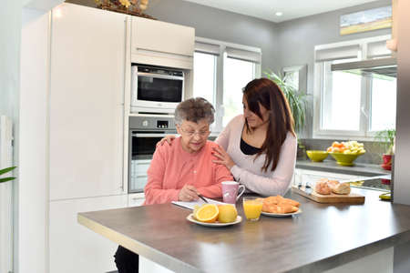 homecare: Elderly woman doing crossword while homecare helps at home