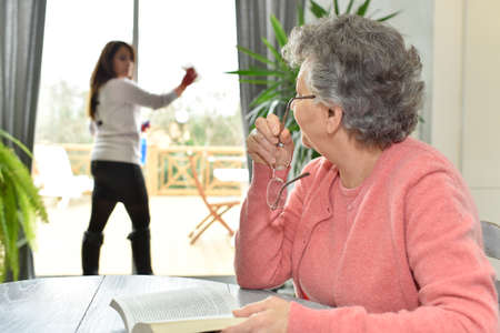 Elderly woman in nursing home reading book