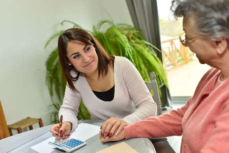 alzheimer: Home helper taking care of elderly womans paperwork Stock Photo