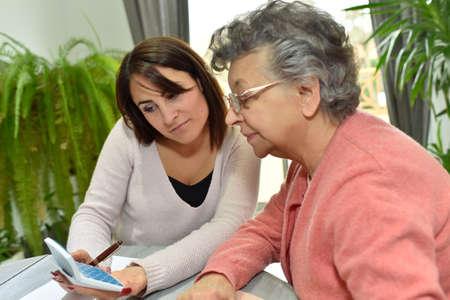 노인 여성의 서류 작업을 돕는 가정 도우미 스톡 콘텐츠