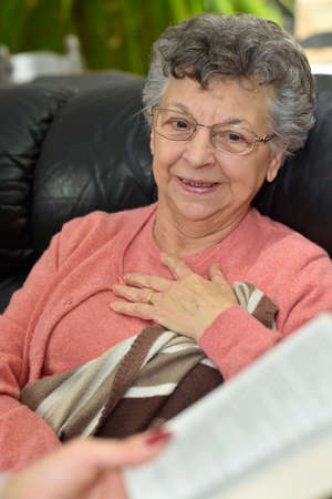 homecare: Homecare reading book to elderly woman