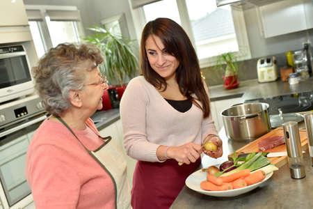 Homecare cooking dinner for elderly woman Foto de archivo