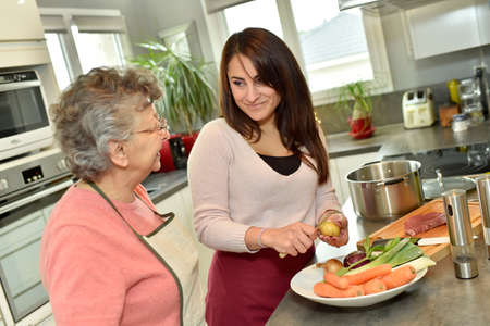 homecare: Homecare cooking dinner for elderly woman Stock Photo