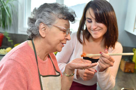 carer: Homecare cooking dinner for elderly woman Stock Photo