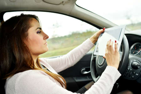 roadmap: Woman driving and looking at roadmap on digital tablet Stock Photo